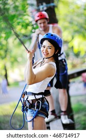 boy and girl climbing on rope road in a special outfit and helmet. The instructor of rock climbing and overcoming obstacles