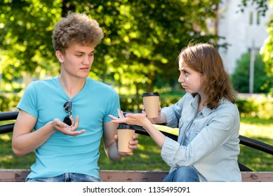 A boy and a girl communicate in nature. In the summer after the lessons on the bench. The concept of misunderstanding. Claims each other. Emotionally gestures with hands. Resentment and disagreement