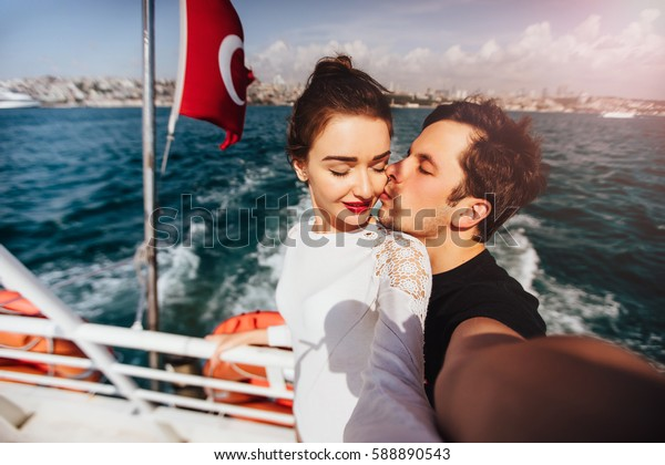 Boy and girl, couple. Make selfie on camera on board a boat cruise vacation. Against the backdrop of the Turkish flag, the sea and the city.