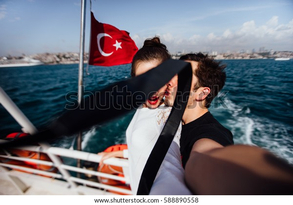 Boy and girl, couple. Make selfie on camera on board a boat cruise vacation. Against the backdrop of the Turkish flag, the sea and the city. Kiss.