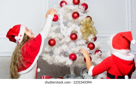 Boy and girl decorating tree. Cherished holiday activity. Kids in santa hats decorating christmas tree. Family tradition concept. Children decorating christmas tree together. Siblings busy decorating.