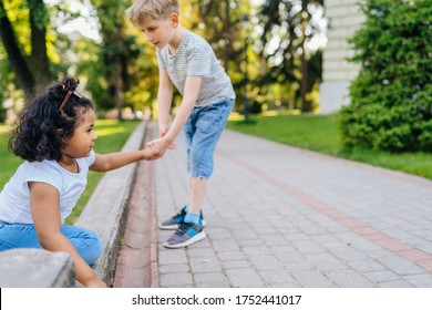 A boy and a girl of different nationalities in white t-shirts play together.Gentle older boy helping a little girl up. Children do not have racism.