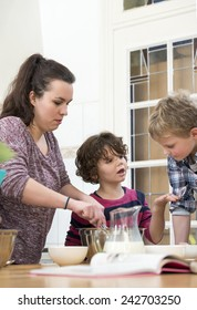 Boy and Girl discussing while mother mixing cupcake batter in kitchen