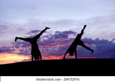 A boy and girl do cartwheels together at sunset on the Rathdrum Prairie in north Idaho.