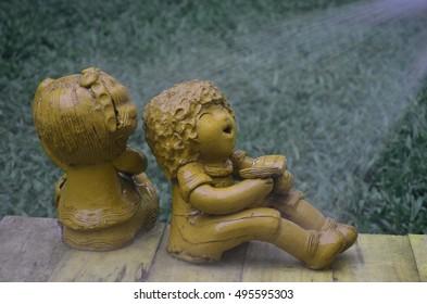 boy and girl doll sitting in garden