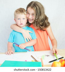 Boy and girl drawing with colourful pencils.
