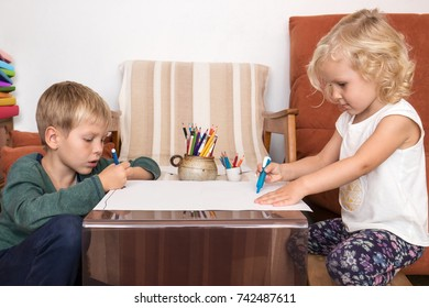 Boy and girl drawing on paper having creative time at home