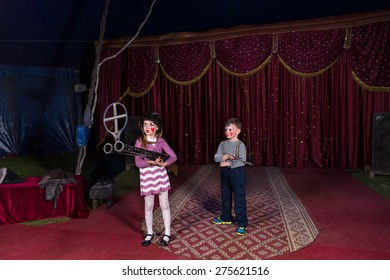 Boy and Girl Dressed as Clowns Standing on Stage Holding Large Double Barreled Shot Gun