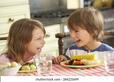 Boy And Girl Eating Meal In Kitchen