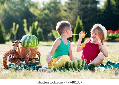 boy and girl eating watermelon in the park