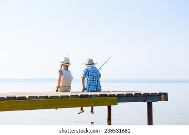 Boy and girl with fishing rods fishing together from a pier