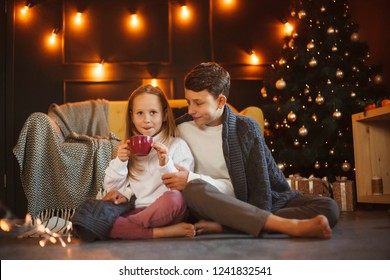 Boy and girl friends or brother and sister with cups of cocoa with marshmallows in Christmas interiors. The concept of Christmas and New Year. Winter time.