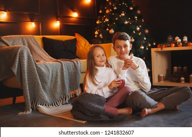 Boy and girl friends or brother and sister сuddling and smiling in the Christmas interiors. The concept of Christmas and New Year. Winter time.