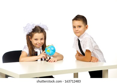 boy and girl with globe isolated in studio