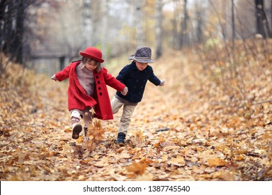 boy and girl in hats walk by the arms in the autumn park, children kick leaves and laugh, concept childhood and a couple, postcards with autumn mood