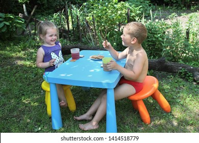 Boy and girl, have breakfast at the table. On the street in a shady garden