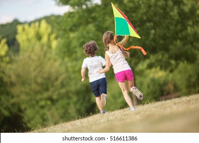 Boy and girl having fun flying a kite in summer