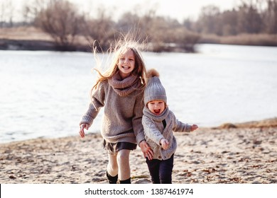 A boy and a girl  having fun outside in early spring in the forest near the water. A sister and brothe together. Friendship and  family concept