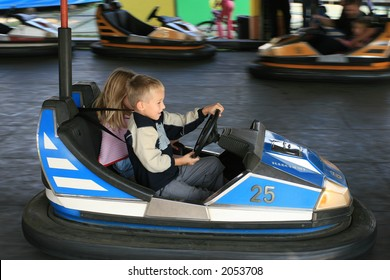 Boy and a girl having a ride in the bumper car at the fun fair