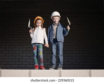 boy and girl in helmets build house