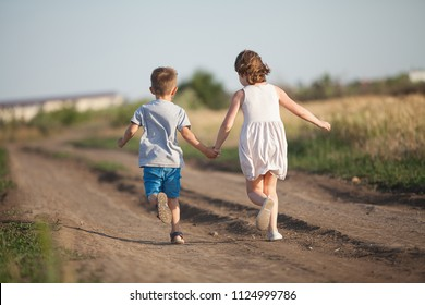 A boy and girl holding hands amicably running across the field in the summer