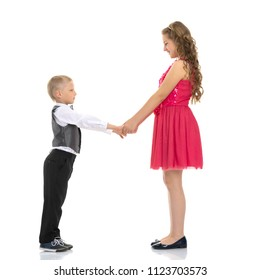 A boy and a girl are holding hands. The concept of friendship, happy childhood. Isolated on white background.