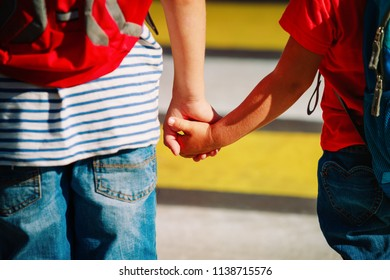 boy and girl holding hands go to school