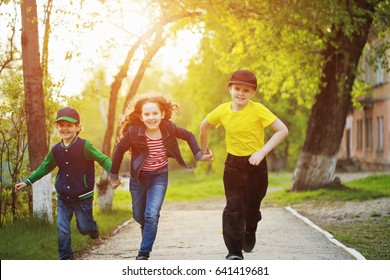 Boy and girl holding hands and running in a park.