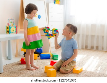 A boy and a girl are holding a heart made of plastic blocks. Brother and sister have fun playing together in the room. Preschool children and educational toys
