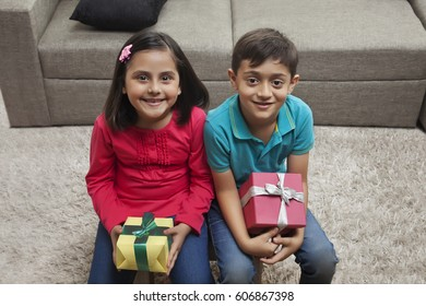 Boy and girl holding presents sitting together in living room