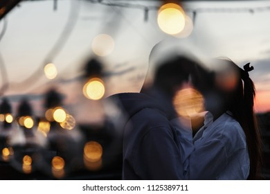 Boy and girl hug each other tender standing on the rooftop in the rays of evening lights