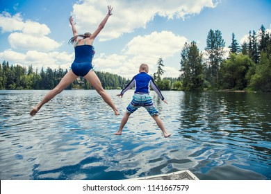 Boy and girl jumping off the dock into a beautiful mountain lake. Having fun on a summer vacation. View from behind