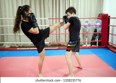 Boy and girl kickbox fighters sparring in the ring