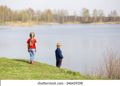 Boy and girl kids playing on grass near lake