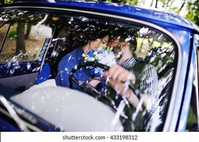 boy and girl kissing in the interior of blue retro car. The bride and groom embracing in a wedding car. photo through the glass. bridal bouquet, blue flowers