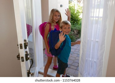 Boy and girl leaving home in the morning to walk through their neighborhood to school with backpacks