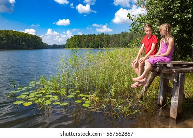 Boy and girl looking at each other while sitting on a wooden pier by a forest lake