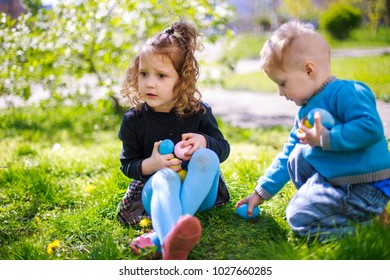 A boy and a girl are looking for Easter eggs among the grass. The brother and sister are sitting on the lawn with colorful eggs in their hands against the backdrop of flowering gardens.