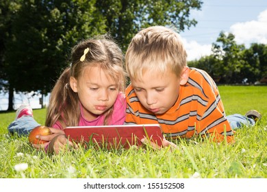 A boy and a girl are looking at the screen of a tablet computer while lying on a green lawn