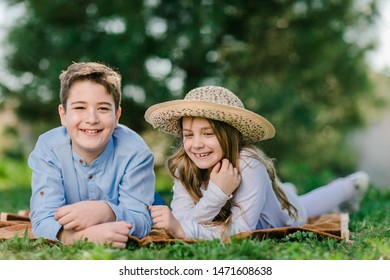 Boy and girl lying at green grass. Happy kids outdoor.
