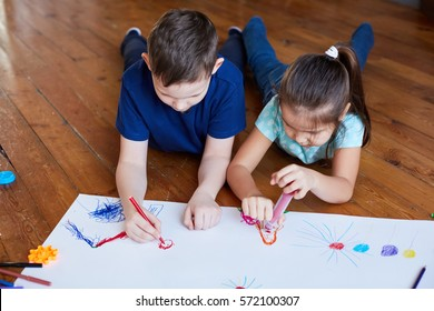 boy and girl lying on the floor and drawing