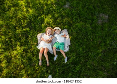 A boy and a girl are lying on the green grass. Top view. Space for text.