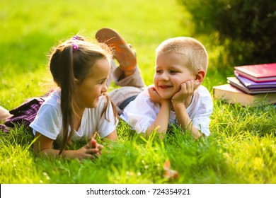 boy and girl are lying in the park on the background of greenery