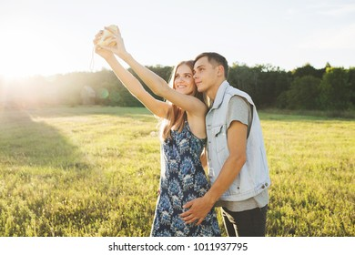 Boy and girl make selfiin summer in field.