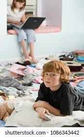 A boy and girl in a messy bedroom