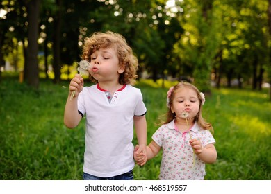 boy and girl on the background of greenery blow on dandelions