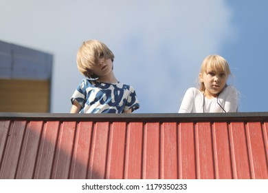 Boy and girl on the open terrace at home against a cloudy blue sky