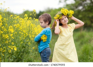 Boy and girl are on a rapeseed field. Girl in a yellow dress with a yellow wreath on her head. A boy is standing nearby, holding a bouquet of flowers in his hands, offended by a girl. The first love.