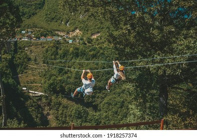 Boy and girl on zip line in mountains in Montenegro, active life, tourism, white clothes, orange helmets
