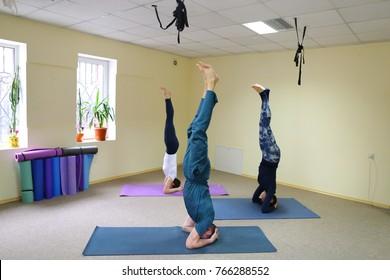 Boy and girl perform yoga asanas, young woman trainer teaches how to keep up. People in great physical form and dressed in comfortable sportswear. On floor covered rugs for fitness. Concept of